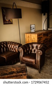 """""""Abruzzo Rocca di Cambio december 102019""""  interior photography of a beautiful vintage leather sofa and armchair. the photo describes the interior of a beautiful renovated industrial style pub"""