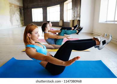 Abs workout, sports, training, healthy and active lifestyle. Group of sporty women doing exercise in gym together