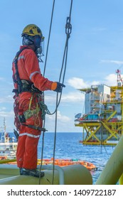 Abseiler with fall protection device kit standing on oil and gas platform structure with background blue sea and sky.