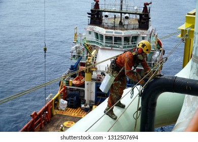 An abseiler wearing Personal Protective Equipment (PPE) standing on pipeline for painting activities with background marine vessel floating at the sea.