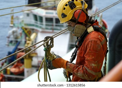 An abseiler wearing Personal Protective Equipment (PPE) such as respiratory protection and yellow hard hat check the condition of access rope knot prior to start work.