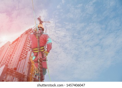 abseiling worker on high wear dresses and safety man with harness concept on steel structures success from work in site construction on blue sky background.