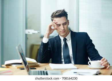Absent-minded businessman contemplating at coffee-break in office