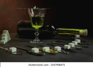 Absinthe bottle with a glass cup and sugar cubes. Absinthe ritual
