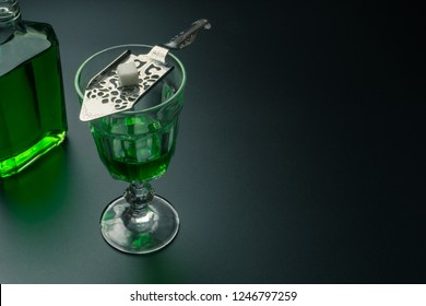 an absinthe bottle, a glass of absinthe and a stainless steel slotted spoon with the sugar cube on the table