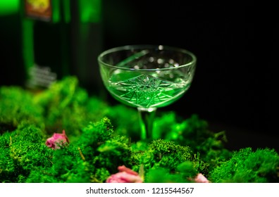 Absinthe glass. Composition with bottle and leaves of Artemisia absinthium.