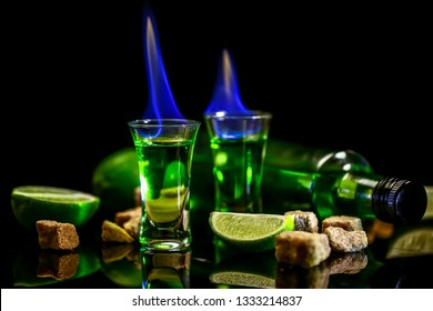 absinthe in glass with lime slices on dark background. Bottle of absinthe and glasses with burning. cube brown sugar. free space for text. the concept of elite alcohol.
