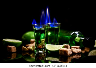 absinthe in glass with lime slices on dark background. absinthe poured into a glass.absinthe poured into a glass. free space for text. the concept of elite alcohol.