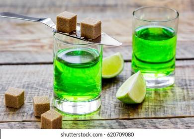 absinthe in glass with lime slices on wooden background