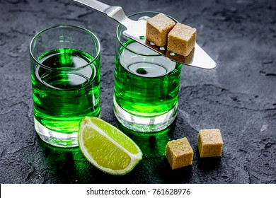 absinthe in glass with lime slices on dark background