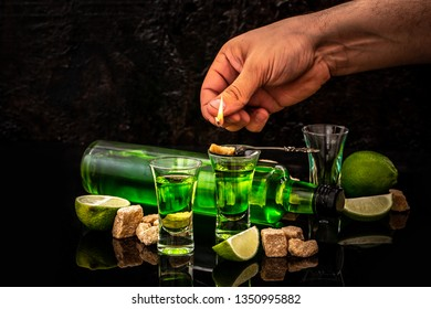 absinthe in glass with lime slices and sugar cubes. absinthe poured into a glass. space for text.