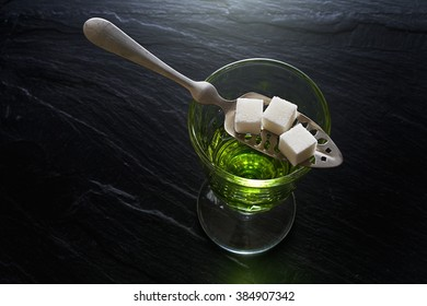 absinthe in pontarlier glass and spoon with sugar cubes