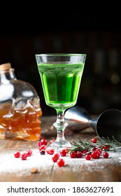 Absinthe is poured into a beautiful old glass, stands on the bar counter. sugar is beautifully sprinkled near the glass and red berries lie