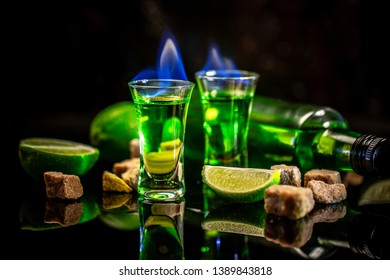 absinthe poured into a glass. alcoholic drink with brown sugar and lime. Absinthe or mint liquor shot.