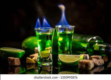 absinthe poured into a glass. in the background is a bottle of absinthe with brown sugar and lime isolated on black background. space for text