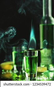 absinthe poured into a glass. on top is a spoon with burning sugar. in the background is a bottle of absinthe.  on a background of smoke