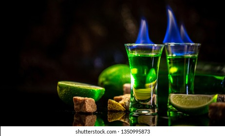 absinthe poured into a glass. Photo of a glass of absinthe and sugar cubes isolated on black background. space for text.