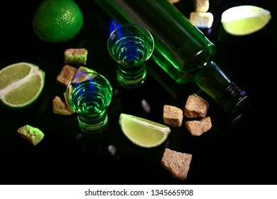 absinthe poured into a glass. absinthe shots with sugar cubes. Bottle of absinthe and glasses with burning. free space for text. the concept of elite alcohol.