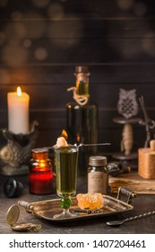 Absinthe poured into a tall glass. On top is a spoon with burning sugar. In the background is a bottle of absinthe. On a black wooden background with burning candles. Romantic style.