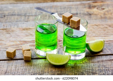 absinthe shots with lime slices and sugar on wooden table background