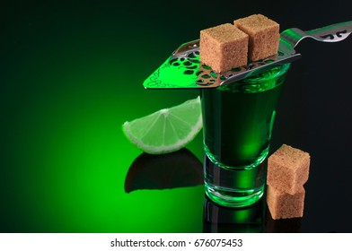absinthe shots with lime slices and sugar on dark green background
