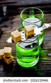 absinthe shots with sugar cubes on wooden table background