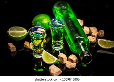 absinthe shots with sugar cubes. absinthe poured into a glass. bottle of absinthe with brown sugar and lime isolated on black background. space for text.