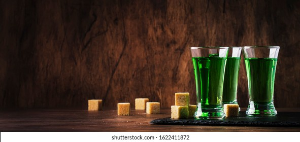 Absinthe - strong alcoholic drink, green bitter wormwood tincture in glasses on the old wooden table, place for text