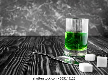 absinthe with sugar cubes and spoon on wooden background