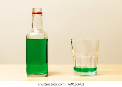 Absinthe (traditional green wormwood alcohol) bottle and glass on the table