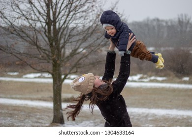 absolute happiness and innocent unconditional love young mother and adorable babyboy son holding above her head in winter with snow