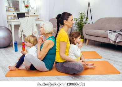 Absolute tranquility. Pleasant calm family sitting on yoga mats while practicing yoga together