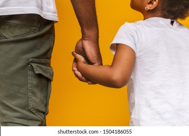 Absolute trust. Little african girl holding her daddy hand and looking at him, orange background