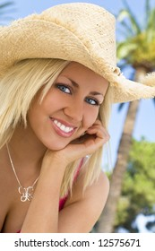 An absolutely gorgeous blond haired blue eyed young woman sits in front of palm trees laughing in golden sunshine while wearing a straw cowboy hat