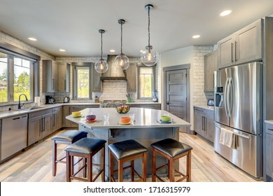 Absolutly stunning kitchen interior with grey tone of brown muted natural tones with light hardwood and rustic modern island with colorful plates.