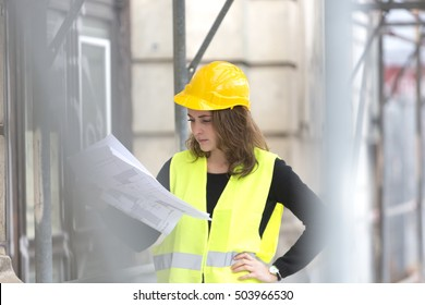 Absorbed female engineer checking office blueprints among scaffolding. Selective focus