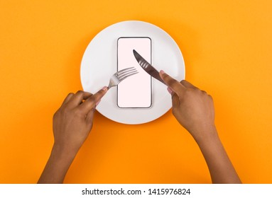 Absorption of information. African american woman eating blank smartphone with knife and fork, top view, mockup