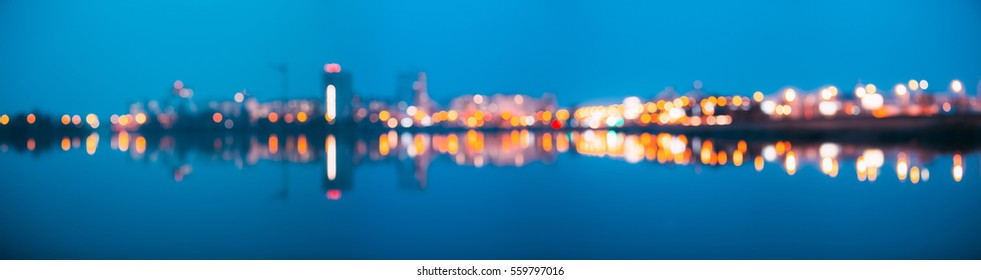 Absract Blurred Bokeh Architectural Urban Backdrop With Reflections In Water. Real Blurred Colorful Bokeh Panoramic Background With Defocused Lights