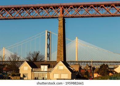 Absract image of the three Forth Bridges at North Queensferry, Scotland towering behind a local town house - morning sunlight illuminates the scene
