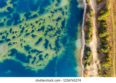 Abstract aerial image of a deep blue gravel lake with sandbanks almost reaching the surface of the water