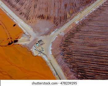 Abstract Aerial View of Red Tailing Ponds With Roads and Canals on a Sunny Summer Day in