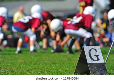 Abstract of American youth football goal marker on the line with out of focus players in the background playing the game.