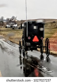 Abstract of Amish Buggy Driving through the Rain on Edge of Wet Road with Farmland in the Background; Raindrops Blurring Foreground