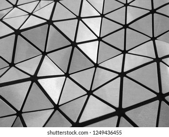 Abstract architectural background of triangular shapes on an undulating grey metallic surface