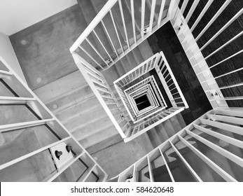 Abstract architecture background, square concrete stairway perspective, looking down in a stairwell, black and white photo