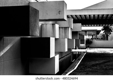 Abstract architecture made of concrete with square blocks sticking out of the wall create a three-dimensional aspect.