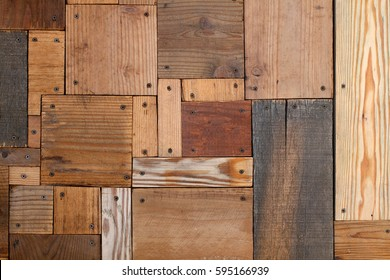 Abstract art background of varied weathered plywood and plank board rectangles and squares nested to from smooth surface of aged yellow and orange wood grains dotted with black screws in corners