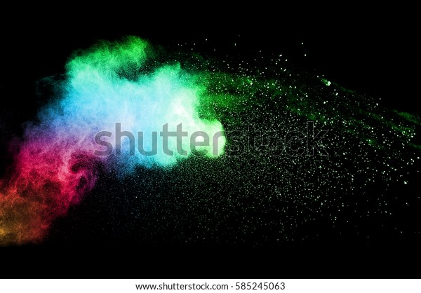 Abstract art colored powder on black background. Frozen abstract movement of dust explosion multiple colors on black background. Stop the movement of multicolored powder on dark background.