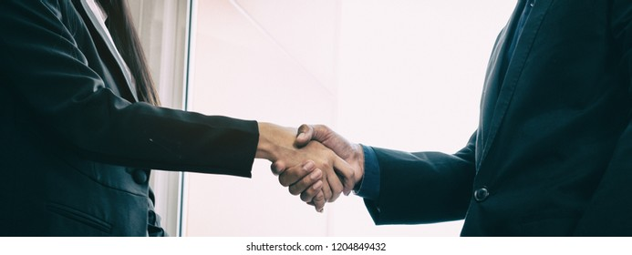 The abstract art design background of business workers are shaking hand,business hand sign of success,team work,collaborator,blurry light around