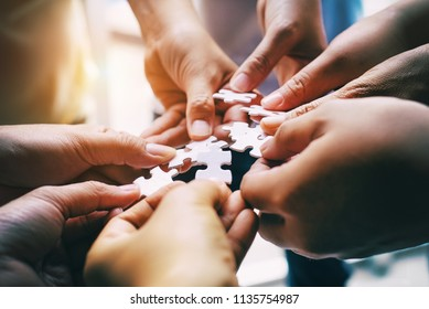 The abstract art design background of human hands assembling jigsaw puzzle,searching for right match,teamwork support to find common solution concept,blurry light around.